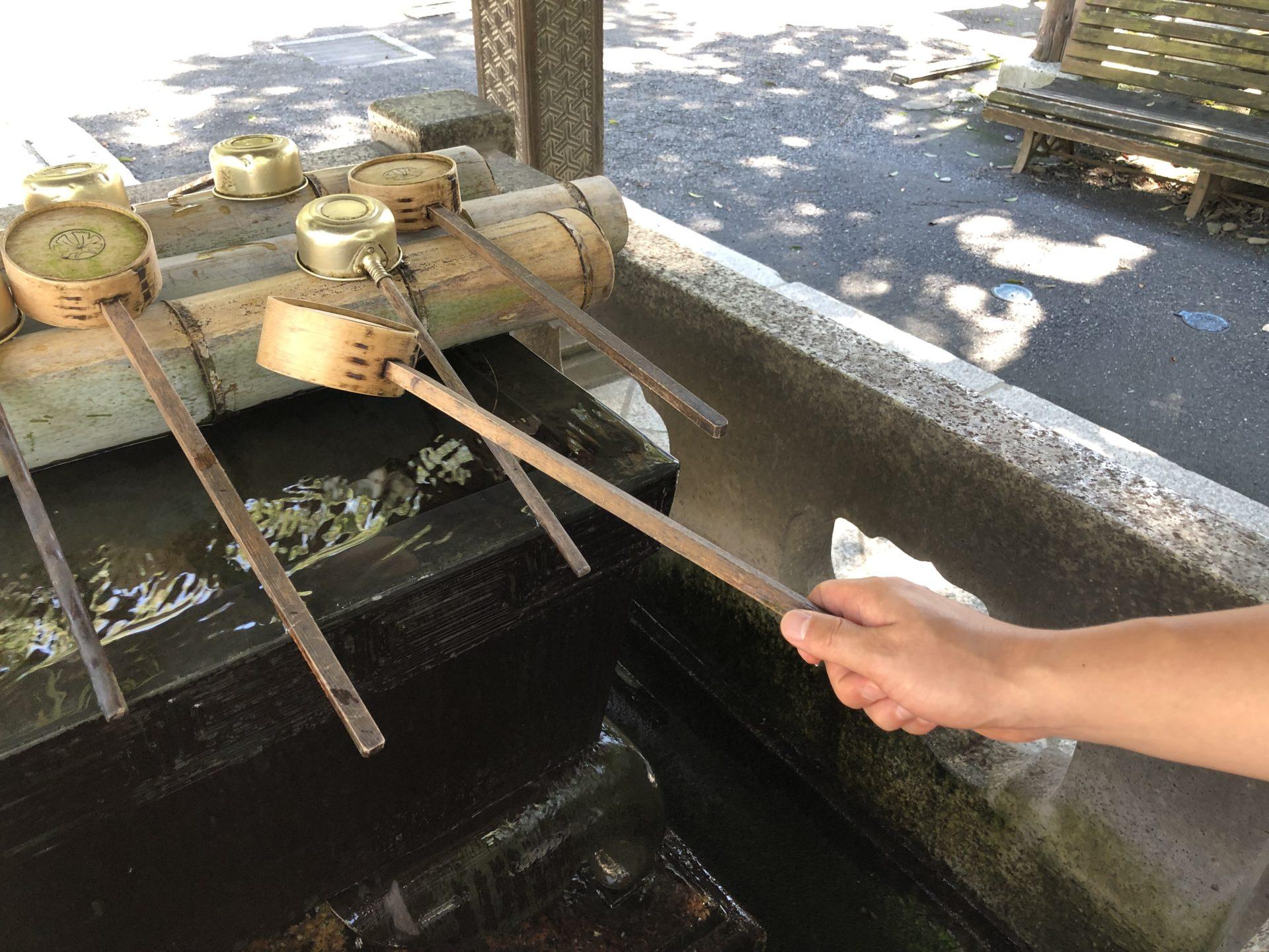 右手で柄杓を持って水を汲む
