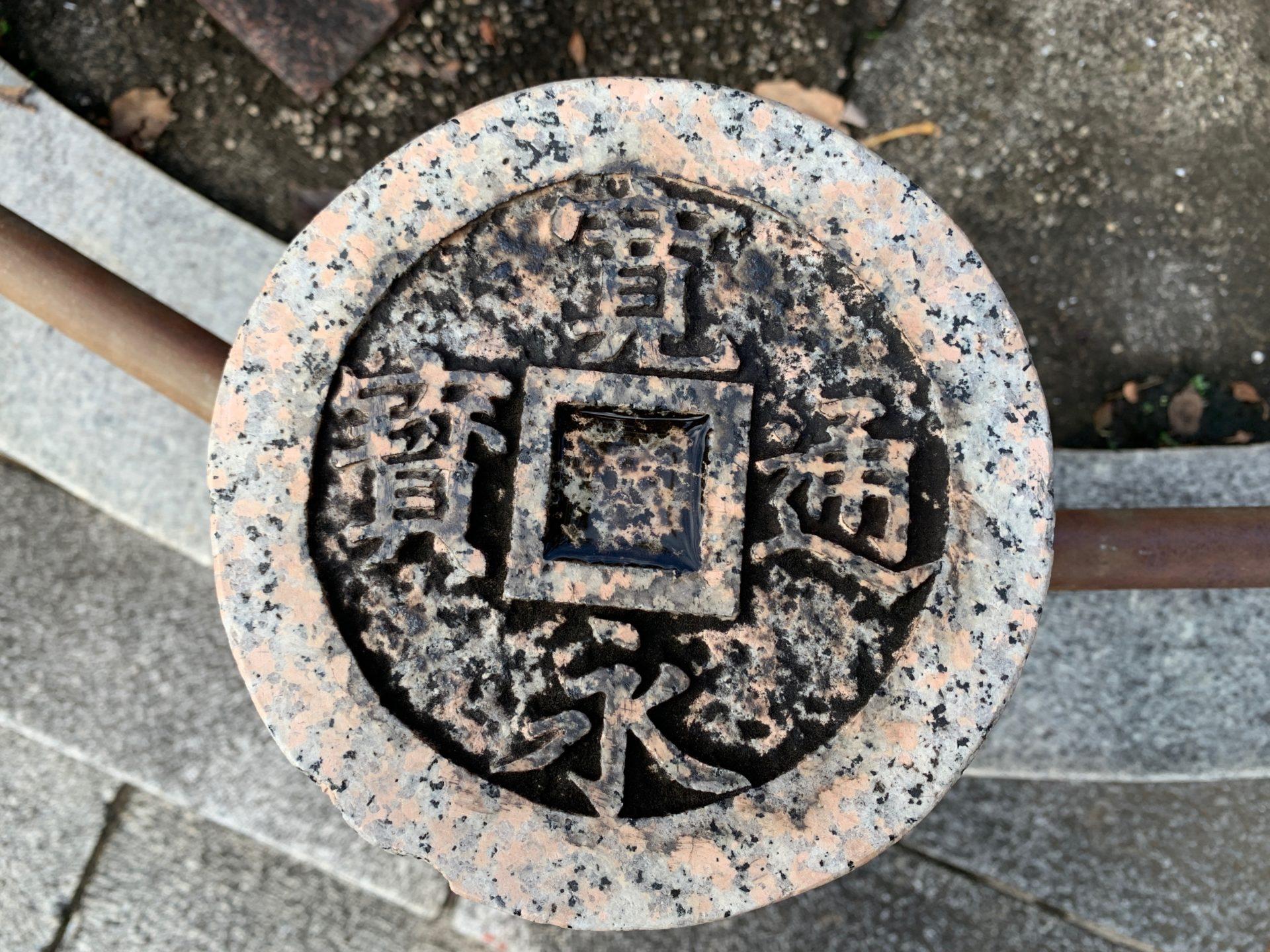 寛永通寶が刻まれている石の柵